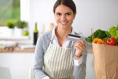 Femme souriante, shopping en ligne à l'aide d'ordinateur et la carte de crédit dans la cuisine — Photo