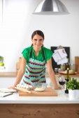 Glimlachend jonge vrouw in de keuken, geïsoleerd op achtergrond — Stockfoto