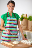 Smiling young woman in the kitchen, isolated on background — Stock Photo