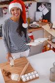 Mulher jovem feliz sorrindo feliz se divertindo com os preparativos de natal usando o chapéu de papai noel — Fotografia Stock