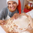 Happy young woman smiling happy having fun with Christmas preparations wearing Santa hat — Stock Photo