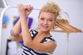 Beautiful young stylist near rack with hangers — Stock Photo