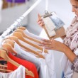 Beautiful young stylist near rack with hangers — Stock Photo #54510441