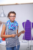 Smiling fashion designer standing near mannequin in office — Stock Photo
