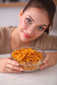 Smiling attractive woman having breakfast in kitchen interior — Stock Photo