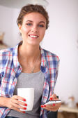 Smiling woman holding her cellphone in the kitchen — Stock Photo