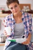 Woman reading mgazine In kitchen at home — Stock Photo