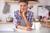 Smiling woman with cup of coffee and newspaper in the kitchen — Stock Photo
