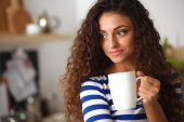 Portrait of young woman with cup against kitchen interior background. — Stock Photo