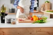 Junge frau schneiden gemüse in der küche — Stockfoto