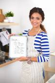 Woman in the kitchen at home, standing near desk with folder — Stock Photo
