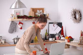 Woman using a laptop while drinking juice in her kitchen — Stock Photo
