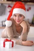 Leende ung kvinna i köket, isolerade på jul bakgrund — Stockfoto