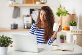 Smiling young woman with coffee cup and laptop in the kitchen at home — Stock Photo
