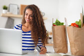 Smiling woman online shopping using computer and credit card in kitchen — Stok fotoğraf