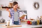 Ung kvinna läser kokbok i köket, letar recept — Stockfoto