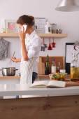 Portrait a smiling woman text messaging of vegetables in kitchen at home — Stock Photo