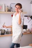 Portrait a smiling woman with phone  of vegetables in kitchen at home — Stock Photo
