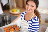 Kvinnan är att göra tårtor i köket — Stockfoto