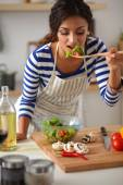 Young woman eating fresh salad in modern kitchen — Stock Photo