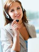 Businesswoman talking on the phone while working on her compute — Stock Photo