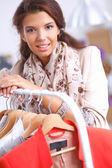 Krásná mladá kadeřnice u regálu s věšáky — Stock fotografie