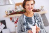 Ritratto di giovane donna con coppa contro backgr interni cucina — Foto Stock