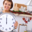 Happy young woman showing clock in christmas decorated kitchen — Stock Photo #54750001
