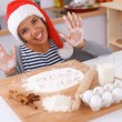 Happy young woman smiling happy having fun with Christmas preparations wearing Santa hat — Stock Photo #55837915