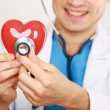 A doctor with stethoscope examining red heart, isolated on white background — Stock Photo #55838205