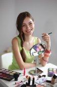 Giovane donna bellissima fare make-up vicino specchio, isolato su sfondo grigio — Foto Stock