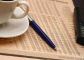Cup of coffee near press and pen — Stock Photo