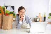 Beautiful young woman cooking looking at laptop screen with receipt in the kitchen — Stock Photo