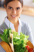 Happy young  woman with shopping bag full of vegetables — Stock Photo