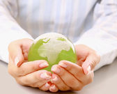 Hands holding a green earth, isolated on white background — Stockfoto