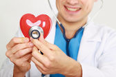 A doctor with stethoscope examining red heart, isolated on white background — Foto Stock