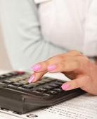Businesswoman doing some paperwork at her desk using a calculator — Stock fotografie