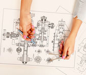 Female architect working with blueprints at office desk — Stock Photo