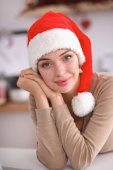 Smiling young woman in the kitchen, isolated on christmas background — Stock Photo