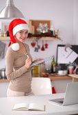 Улыбается молодая женщина на кухне, изолированные на новогодний фон — Стоковое фото