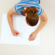 Top view of cute young woman thinking with a pen in her mouth while lying on floor and drawing. — Stock Photo #57561905