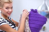 Smiling fashion designer fixing dress on  mannequin in a studio — Foto de Stock