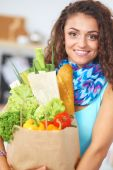 Young woman holding grocery shopping bag with vegetables Standing in the kitchen. — Stock Photo