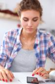 Smiling woman online shopping using computer and credit card in kitchen — Stock Photo