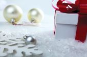 Decorative white gift box with a red bow a background bokeh. — Stock Photo
