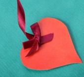 Heart with red tape isolated on green background — Stock Photo
