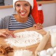 Happy young woman smiling happy having fun with Christmas preparations wearing Santa hat — Stock Photo #58169057