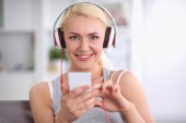 Young beautiful woman at home sitting on sofa and listening music — Stock Photo