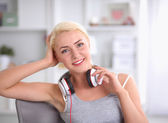 Young beautiful woman at home sitting on sofa and listening music — Foto de Stock
