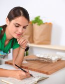 Felice bella donna in piedi nella sua cucina scrivendo su un quaderno a casa — Foto Stock